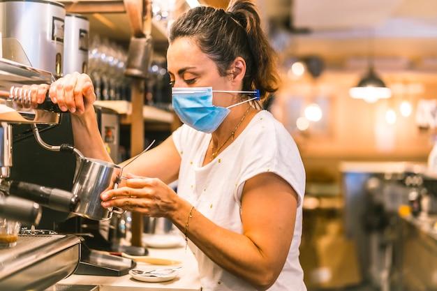 Een serveerster met een gezichtsmasker in een bar. koffie zetten met melk met de koffiemachine