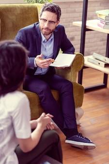 Een sessie hebben. aardige bebaarde man met een notitieboekje tijdens een gesprek met zijn patiënt