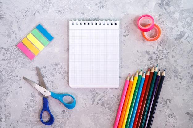 Een set briefpapier. kladblok, kleurpotloden, schaar, kleurrijke stickers en plakband