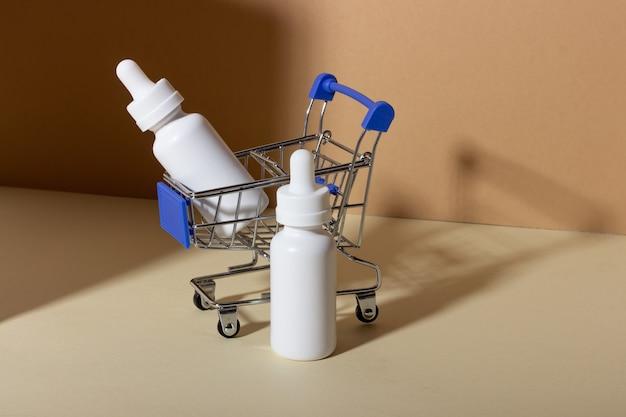 Een set cosmetische producten met een druppelaar voor gezichtsverzorging in een winkelwagentje op een gele achtergrond met schaduwen. het concept van het kopen van cosmetica, online winkelen
