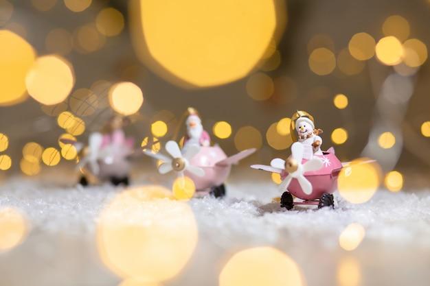 Een set decoratieve beeldjes met kerstthema, kerstman herten en sneeuwpop in roze vliegtuigen met propeller,,