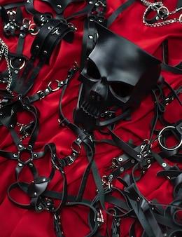 Een set erotische speeltjes voor bdsm. seksslavernijspel met zweep, prop en leren gezichtsmasker. intieme seksspelletjes leren riemen op rode achtergrond
