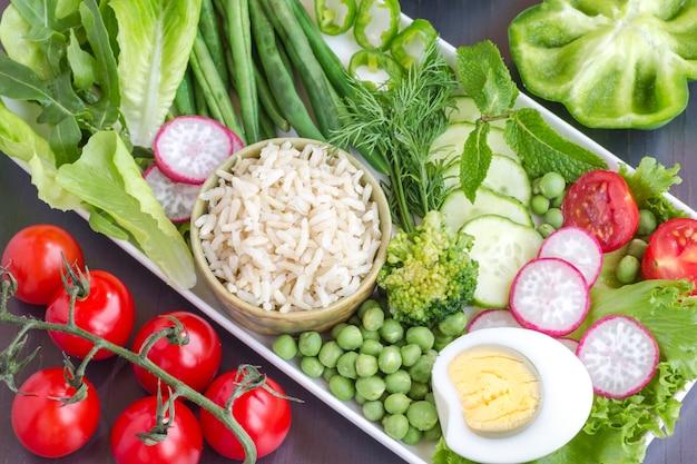 Een set groenten met rijst en ei: erwten, asperges, radijs, broccoli, sla, tomaten.