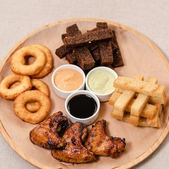 Een set hapjes voor bier croutons frietjes uienringen kaasstengels en drie sauzen