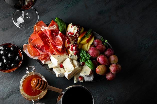 Een set hapjes voor wijn, jamon, pepperoni, kaas, druiven, perzik en olijven op een plaat bovenaanzicht.