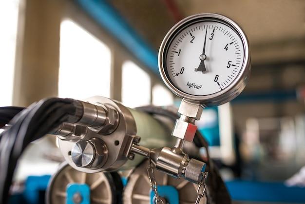 Een set hoogspanningskabels in een gemeenschappelijk mondstuk gedragen op een ijzeren trommel met daarop een barometer