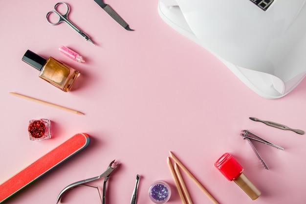 Een set hulpmiddelen voor manicure en nagelverzorging op een roze achtergrond.