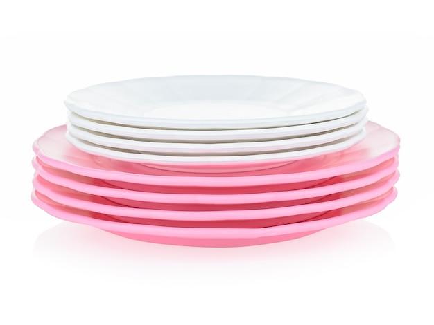Een set kinderservies gemaakt van roze plastic op een witte achtergrond.