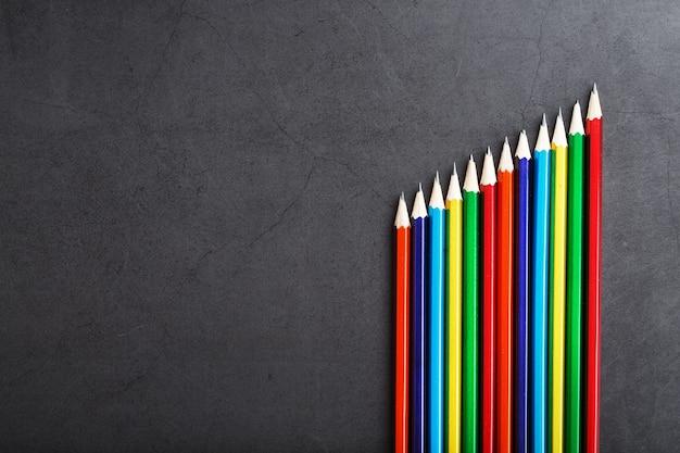 Een set kleurrijke potloden op een gestructureerde donkere achtergrond
