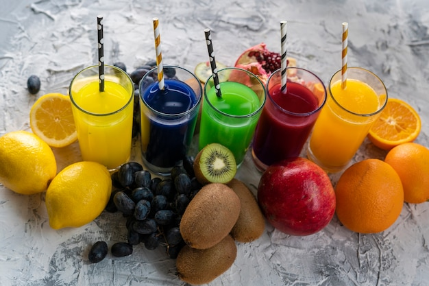 Een set koele verse geperste sappen of cocktails in een glazen gemaakt van sinaasappel, kiwi, citroen, druiven, granaatappels