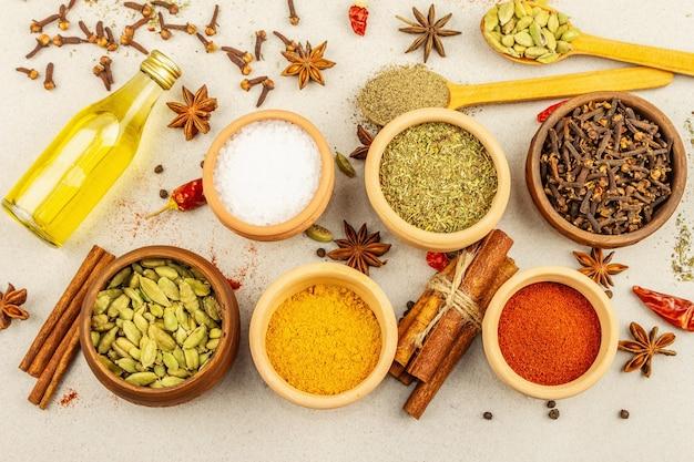 Een set kruiden voor het koken van curry. aromatische specerijen: kurkuma, paprika, kardemom, kaneel, steranijs, chili, zwarte peper, droge kruiden, zout. lichte stenen betonnen achtergrond, bovenaanzicht