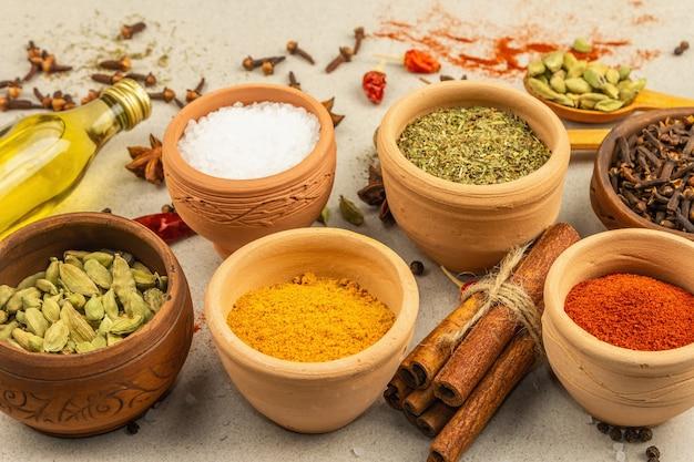 Een set kruiden voor het koken van curry. aromatische specerijen: kurkuma, paprika, kardemom, kaneel, steranijs, chili, zwarte peper, droge kruiden, zout. lichte stenen betonnen achtergrond, close-up