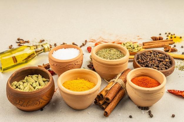 Een set kruiden voor het koken van curry. aromatische specerijen: kurkuma, paprika, kardemom, kaneel, steranijs, chili, zwarte peper, droge kruiden, zout. lichte stenen betonnen achtergrond, kopieer ruimte