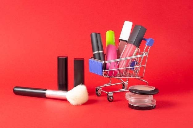 Een set lippenstiftcosmetica en lipglosses, poeder, oogschaduw en een winkelwagentje op een felrode achtergrond. het concept van het kopen van cosmetica, online winkelen, vakantie