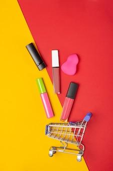 Een set lippenstiftcosmetica en lipglosses, poeder, oogschaduw en een winkelwagentje op een felrode en gele achtergrond. het concept van het kopen van cosmetica, online winkelen, vakantie