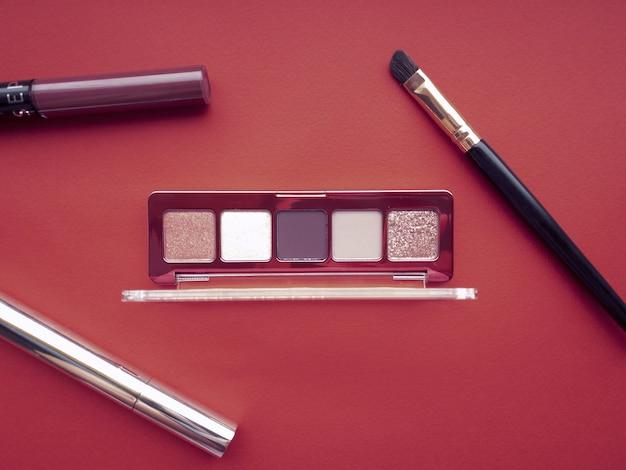 Een set make-upproducten, waaronder oogschaduw, lipgloss, mascara, make-upborstel en markeerstift op rode achtergrond. schoonheidsconcept.