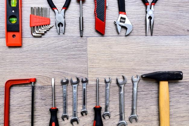 Een set met gereedschap op een houten tafel. hamer, schroevendraaier, gayachnye sleutels, tangen, kniptangen. bovenaanzicht