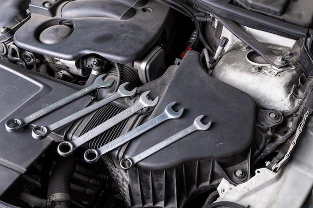 Een set metalen sleutels van verschillende afmetingen ligt onder de motorkap van de auto op een oliekoeler. concept autoreparatie en hulpmiddelen in de autodienst