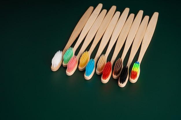 Een set milieuvriendelijke antibacteriële tandenborstels gemaakt van bamboehout op een donkergroene achtergrond.