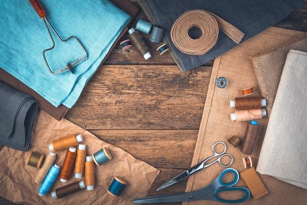 Een set naai-accessoires op een houten achtergrond met ruimte om te kopiëren. bovenaanzicht.