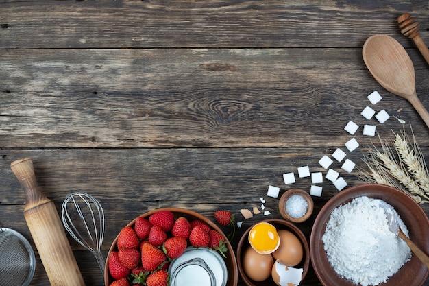 Een set natuurlijke producten voor het maken van een taart op houten ondergrond