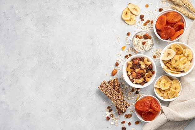 Een set noten en gedroogde vruchten, een mueslireep en rozijnen op een grijze muur. culinaire wand met ruimte om te kopiëren. gezond eten.