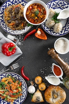 Een set oosterse gerechten in borden met traditionele oezbeekse ornamenten - pilaf met lamsvlees, manti, lagman-soep, groentesalade, tandoor tortilla's, salsa, sauzen en kruiden.