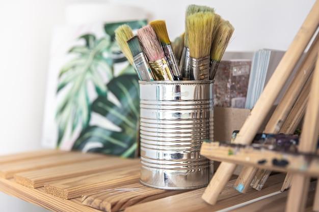 Een set penselen om te schilderen in een blikje op een plank in de werkplaats