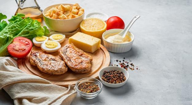 Een set producten voor het maken van caesarsalade op een grijze achtergrond met ruimte om te kopiëren. koken concept.