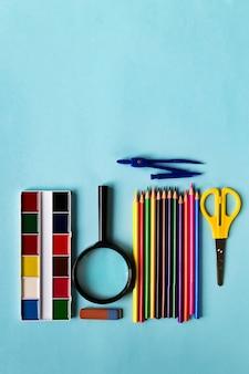 Een set schoolbenodigdheden. vergrootglas, potloden, liniaal, schede, waterverf op een blauw papier achtergrond met ruimte voor tekst.