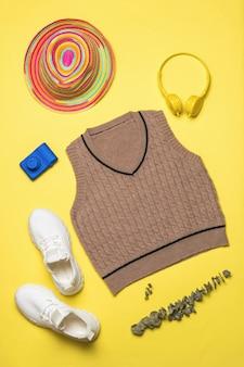 Een set stijlvolle kleding en schoenen op een gele achtergrond. modieuze klassieke gebreide kleding.