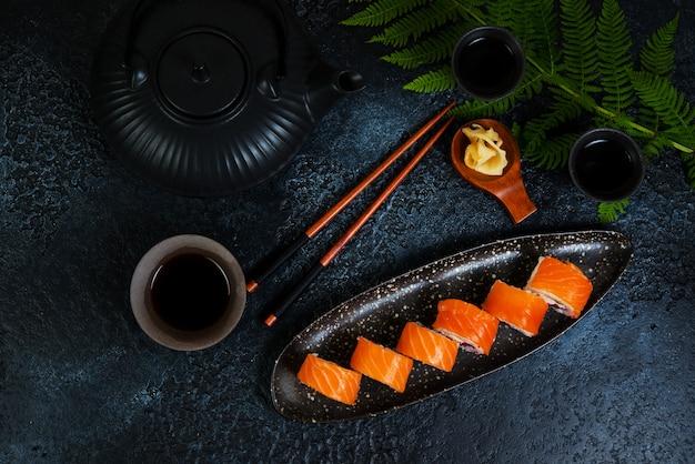 Een set sushi-broodjes philadelphia met rode vis en roomkaas ligt in een bordboot. sushi rolt op een zwarte achtergrond met een theepot chinese thee. bovenaanzicht