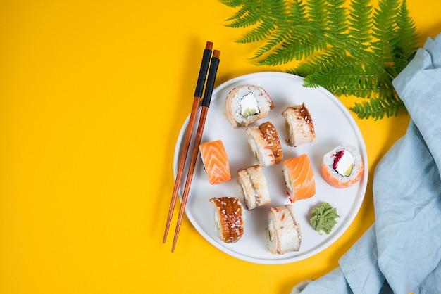 Een set sushi rolt ander type op een gele ruimte. bovenaanzicht. traditionele aziatische gerechten