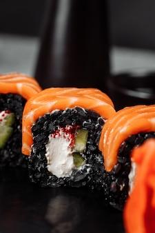 Een set sushi rolt philadelphia met rode vis, roomkaas en zwarte rijst in een plate boat. sushi rolt op een grijze achtergrond.