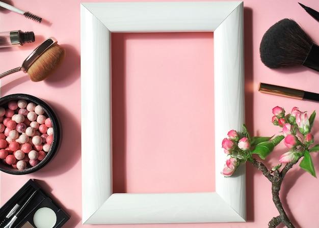 Een set van decoratieve cosmetica op een roze muur met een witte frame in het midden. top viev. plat liggen.