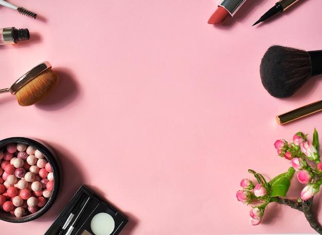 Een set van decoratieve cosmetica op een roze muur. top viev. plat liggen.