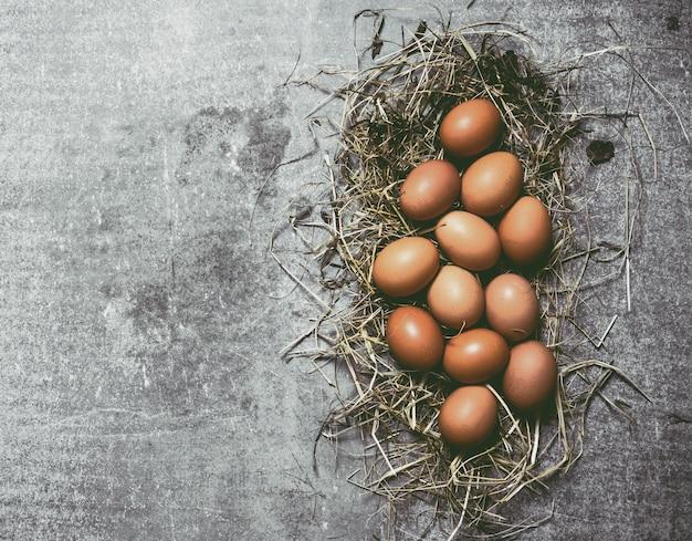 Een set van eieren in hooi op beton. bovenaanzicht
