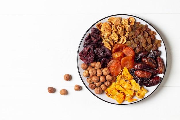 Een set van gedroogde vruchten (appels, dadels, pompoen, abrikoos, kers) en hazelnoten liggend op een witte plaat