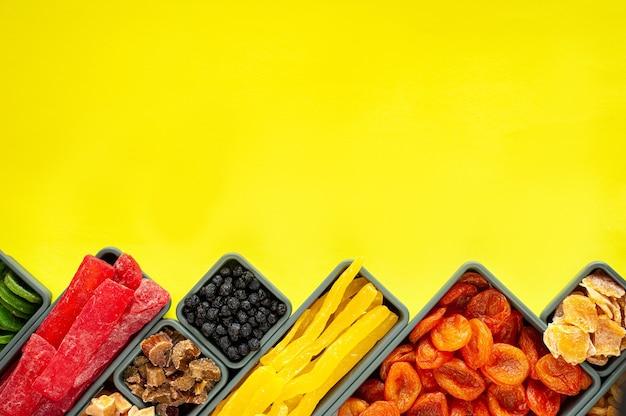 Een set van gedroogde vruchten en gekonfijt fruit in rechthoekige en vierkante dozen op een gele achtergrond.