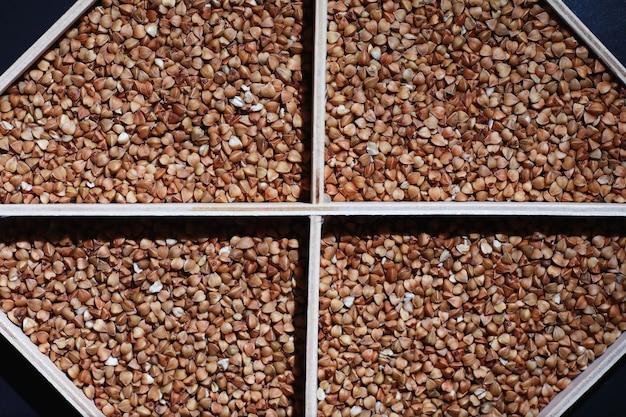 Een set van graan granen. rijst, boekweit en gierstgrutten in een houten dienblad. een kruidenierswinkelreeks van graangewassen. import van graan.