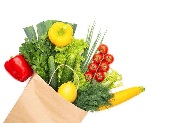 Een set van groenten en kruiden in een papieren zak geïsoleerd op een witte achtergrond. concept: winkelen in een supermarkt of markt en gezond vegetarisch eten.