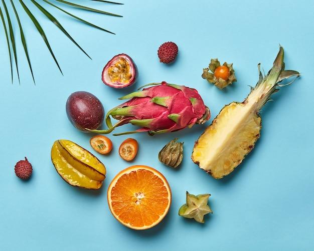 Een set van helften van sinaasappel, ananas, passievrucht en hele carambola's, pitahaya's op een blauwe achtergrond versierd met palmblad uit kopieerruimte. plat leggen