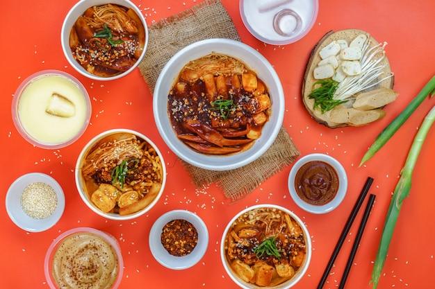Een set van koreaans eten en zoete drank wordt geserveerd op de oranje achtergrond.
