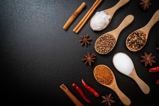 Een set van kruiden en specerijen met lepel en kopieer ruimte op zwart
