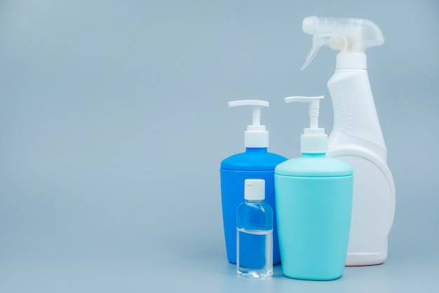 Een set van reinigings- en desinfectieproducten op een grijze achtergrond. close-up met ruimte voor tekst. preventie van coronavirus