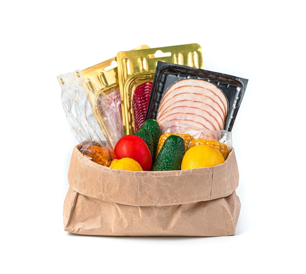 Een set van vers voedsel in een verpakte papieren zak op een wit bureau. zijaanzicht.