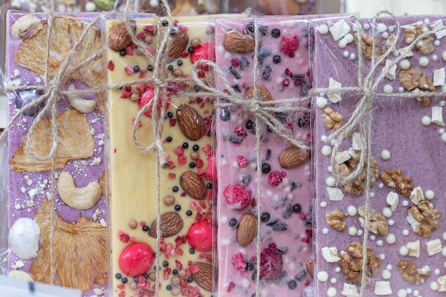 Een set van verschillende chocolaatjes (wit, roze, bruin, bitter, melk) verpakt in een transparante verpakking met een jute touw strik