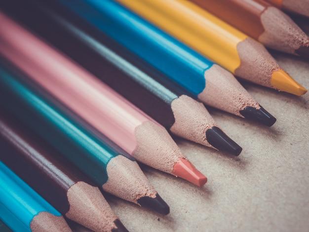 Een set van verschillende kleurpotloden. potloden op een rij op een houten oppervlak.