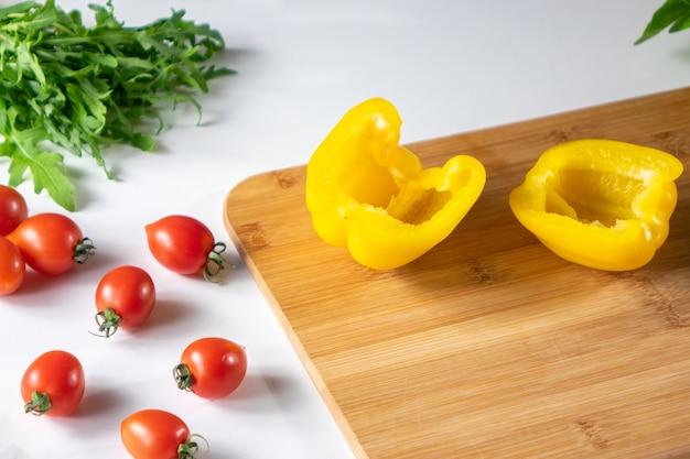 Een set van verse groenten, tomaten, rucola, gele peper op een houten bord op een witte keukentafel met kopie ruimte. foto stap voor stap recept.