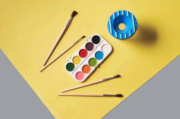 Een set verf in verschillende kleuren in een witte doos op een extreem grijze